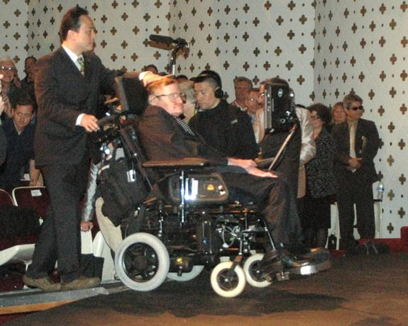"""Dr. Stephen Hawking is brought onstage by a helper to give his presentation, """"The Origin of the Universe,"""" at Caltech on April 16, 2013."""