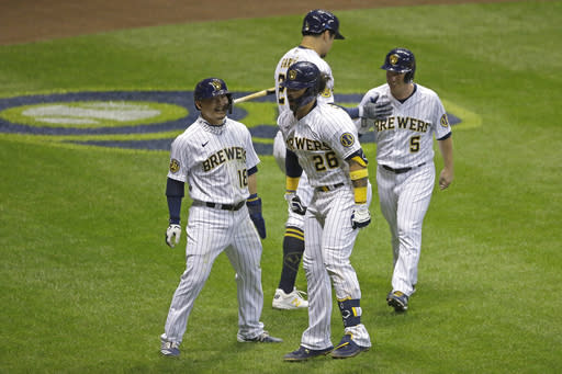 Milwaukee Brewers' Jacob Nottingham (26) celebrates with teammates after hitting a grand slam during the fourth inning of the Brewers' baseball game against the Kansas City Royals on Friday, Sept. 18, 2020, in Milwaukee. (AP Photo/Aaron Gash)