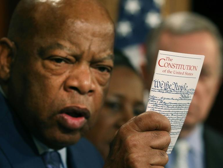 In this file photo taken on March 02, 2016, congressman John Lewis holds up a copy of the US Constitution during a news conference on Capitol Hill with Senate Democrats and members of the Congressional Black Caucus (AFP Photo/MARK WILSON)