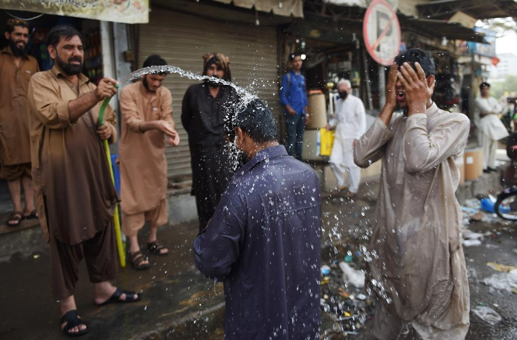 Pakistani workers cool down as a heatwave hits Karachi