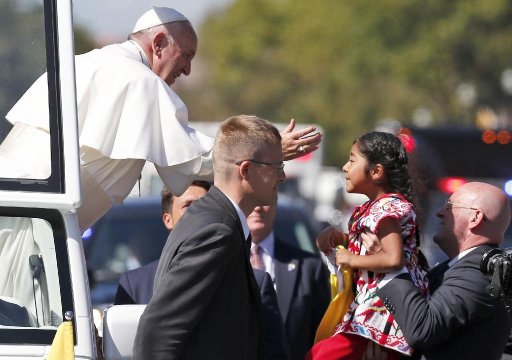 Pope Francis reaches towards five-year-old Sofia Cruz during a parade on September 23, 2015, in Washington, DC (AFP Photo/Alex Brandon)