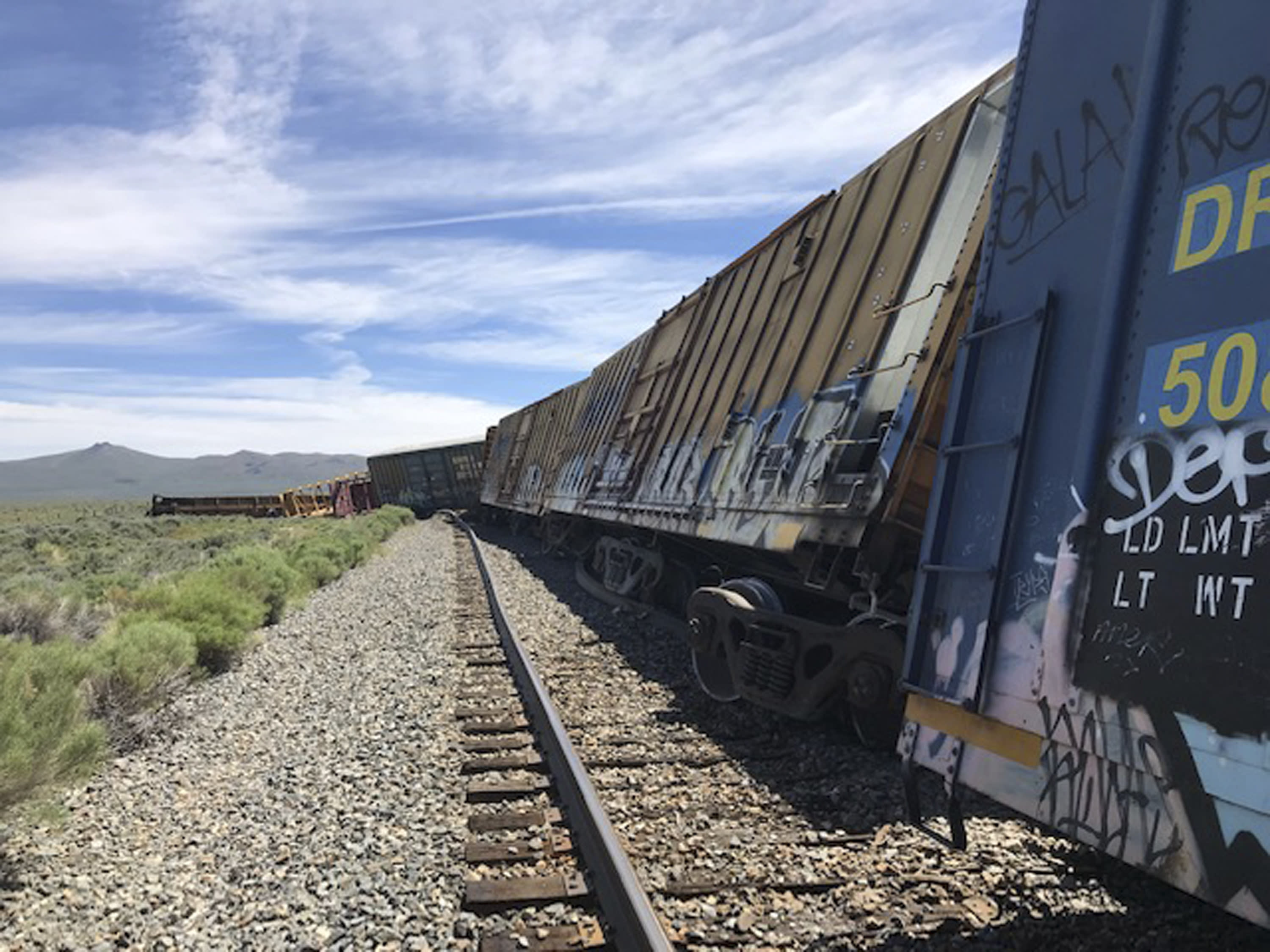 This photo provided by the Nevada Department of Public Safety shows a derailed train Wednesday, June 19, 2019, near Wells, Nev. A train carrying military munitions derailed in the high desert of northeast Nevada, closing an interstate for about an hour before emergency crews determined there was no danger. No injuries were reported. (Nevada Department of Public Safety via AP)