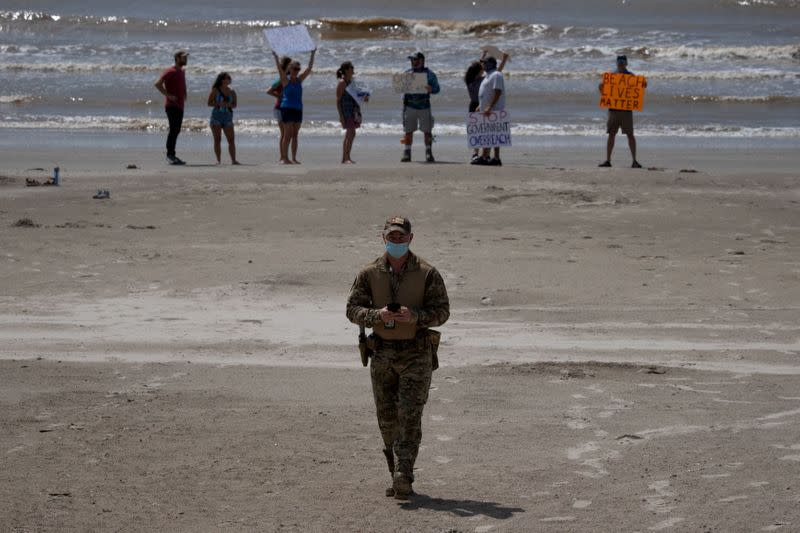 Policeman walks away from residents protesting closed beaches on 4th of July amid the global outbreak of the coronavirus disease in Galveston, Texas