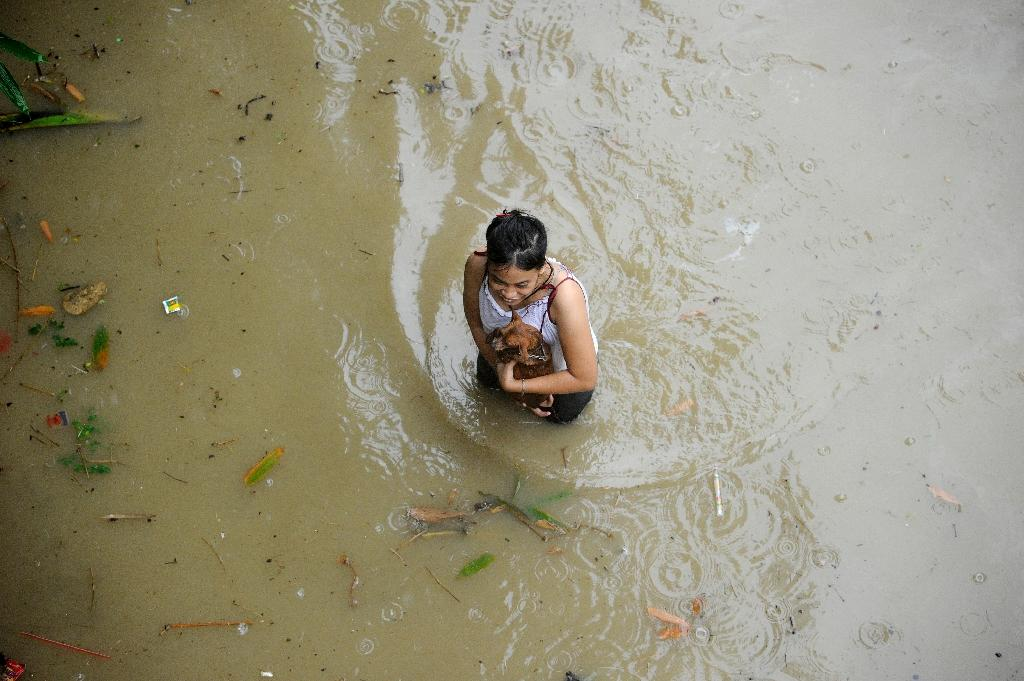 A girl holding her puppy wades through a flooded street in San Mateo, Rizal province on August 13 (AFP Photo/Noel Celis)