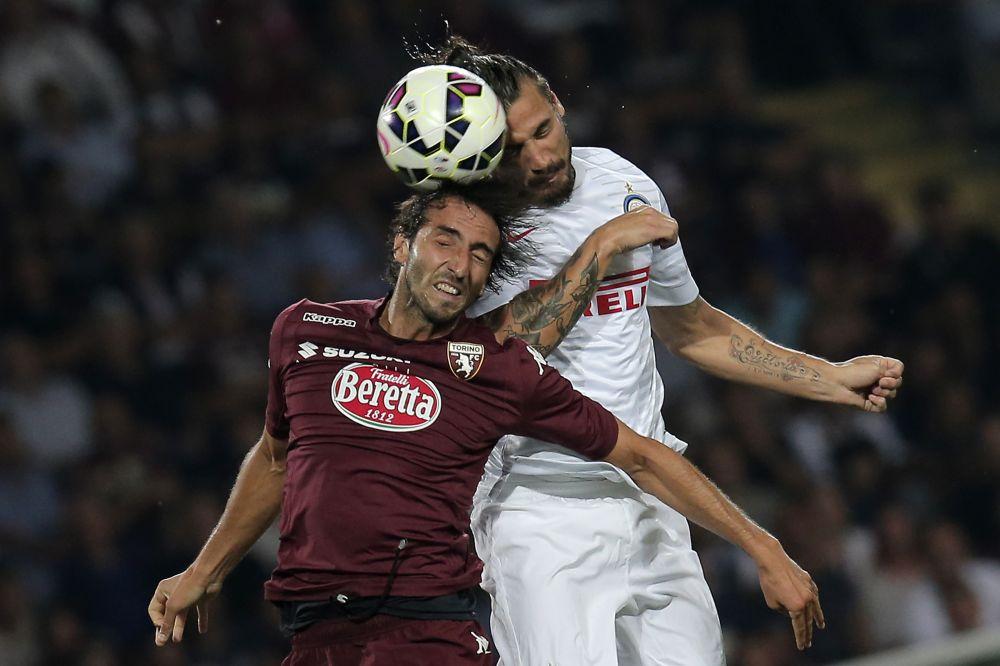 Torino's defender Emiliano Moretti fights for the ball with Inter Milan's forward Pablo Daniel Osvaldo during the Italian Serie A football match on August 31, 2014