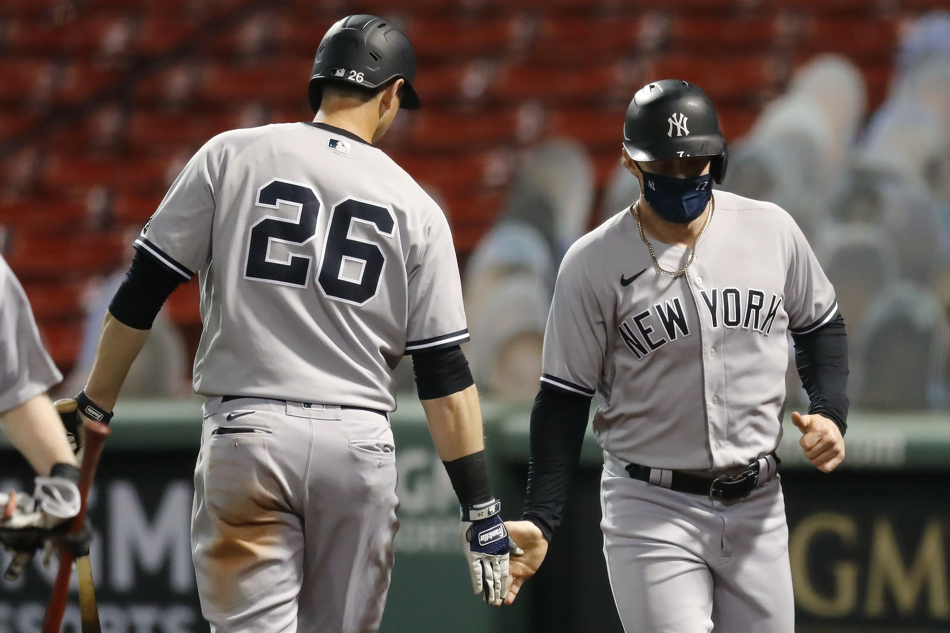 New York Yankees' Clint Frazier celebrates with DJ LeMahieu (26) after scoring on a single by Kyle Higashioka during the fourth inning of a baseball game against the Boston Red Sox, Saturday, Sept. 19, 2020, in Boston. (AP Photo/Michael Dwyer)