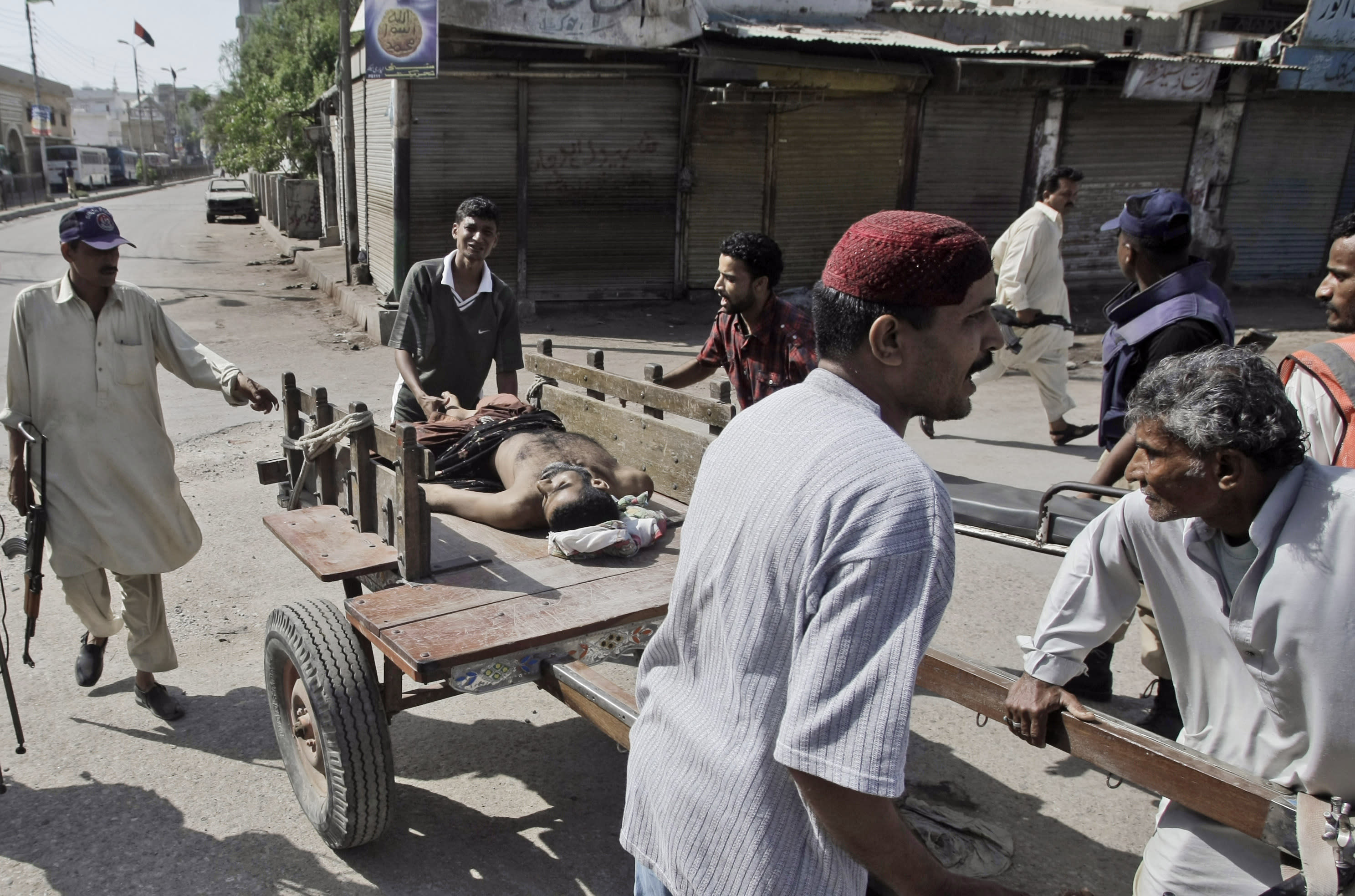 FILE - In this Saturday, April 28, 2012, file photo,Pakistanis use a cart to carry the lifeless body of a civilian away from the site of fighting, during a crackdown operation by Pakistani police commandos against criminals in Karachi's town of Lyari, Pakistan. Over 2,000 people were murdered in Pakistan's largest city last year, but the shooting death of 20-year-old Shahzeb Khan in one of Karachi's most upscale neighborhoods sparked an unusual outcry and highlighted a growing trend of citizens using social media to hold the country's rich and powerful to account. (AP Photo/Fareed Khan, File)