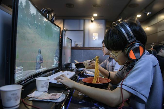 """In a photo taken on July 13, 2018, a customer eats noodles as he plays computer games at an eSports cafe, or """"PC Bang"""", in Seoul. - South Korea enjoys ultra-fast broadband and a vibrant Internet culture, and internet cafes armed with powerful high-end computers catering to school-age gamers can be found on many street corners. (Photo by Ed JONES / AFP) / TO GO WITH SKorea-eSports, FOCUS by JUNG Hawon        (Photo credit should read ED JONES/AFP via Getty Images)"""