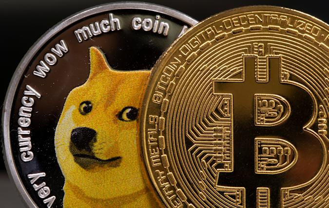 Representations of the virtual currency Dogecoin and Bitcoin are seen in this illustration taken June 16, 2021. REUTERS/Dado Ruvic/Illustration