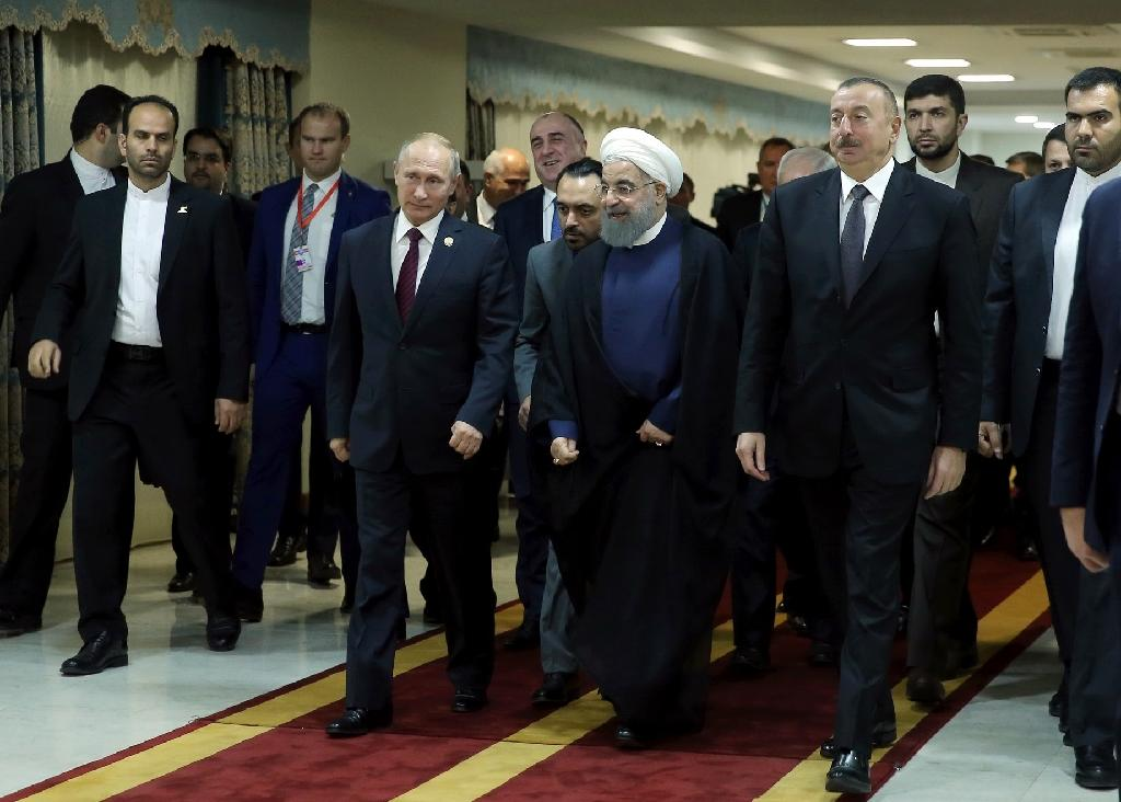 A handout photo provided by the office of Iranian President Hassan Rouhani shows him (C), flanked by Azerbaijan's President Ilham Aliyev (R) and Russian President Vladimir Putin (L) during a meeting in Tehran on November 1, 2017. (AFP Photo/HO)