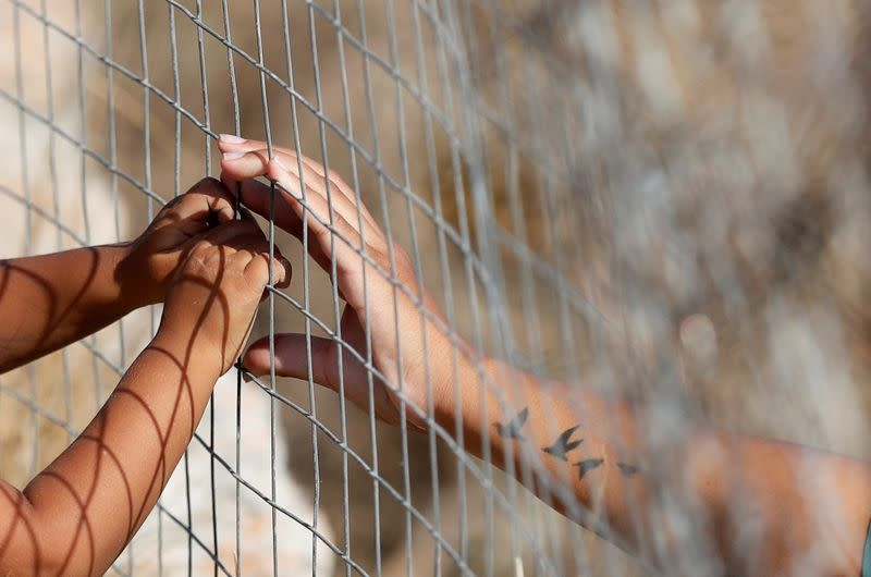 FILE PHOTO: Woman touches hands of a child through a fence at a new temporary camp for migrants and refugees on the island of Lesbos