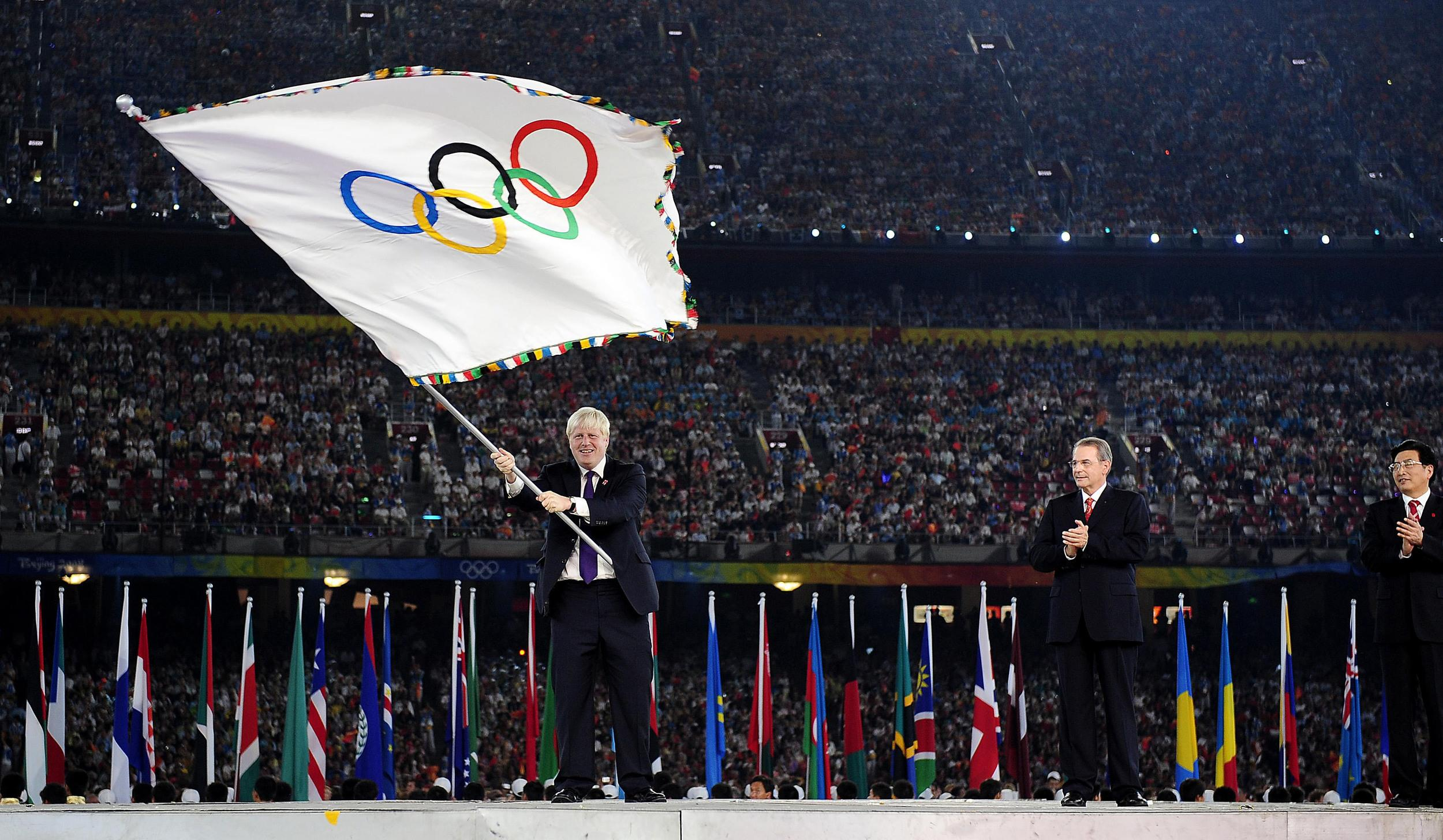 Mayor of London Boris Johnson waves the Olympic Flag during the handover ceremony as President of IOC Jacques Rogge (centre) and Mayor of Beijing Guo Jinlong look on at the National Stadium during the 2008 Beijing Olympic Games, China.