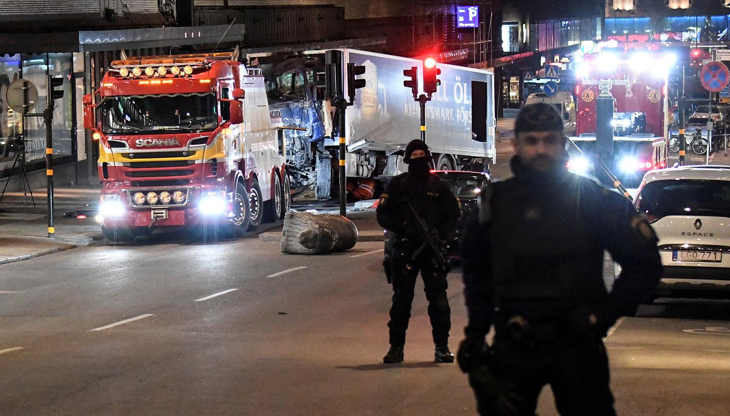<p>Policemen stand guard as tow trucks pull away the beer truck that crashed into the department store Ahlens after plowing down the Drottninggatan Street in central Stockholm, Sweden, April 8, 2017. (Photo: Maja Suslin/TT News Agency/Reuters) </p>