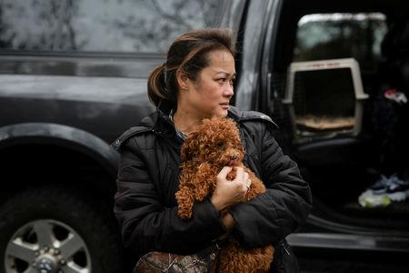 Vanthy Bizzle holds her dog Chewie after returning to the remains of her home for the first time since the Camp Fire forced her to evacuate with her husband in Paradise, California, U.S. November 22, 2018. REUTERS/Elijah Nouvelage