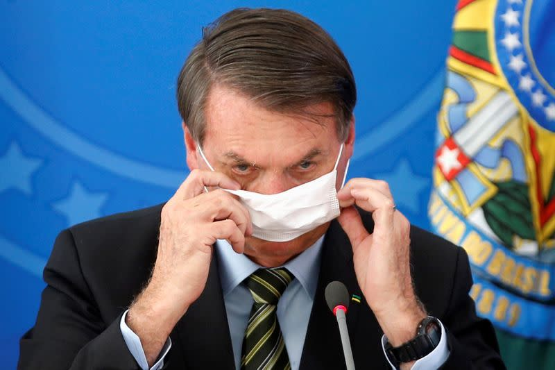 Brazil's President Jair Bolsonaro adjusts his protective face mask during a news conference to announce measures to curb the spread of the coronavirus disease (COVID-19) in Brasilia