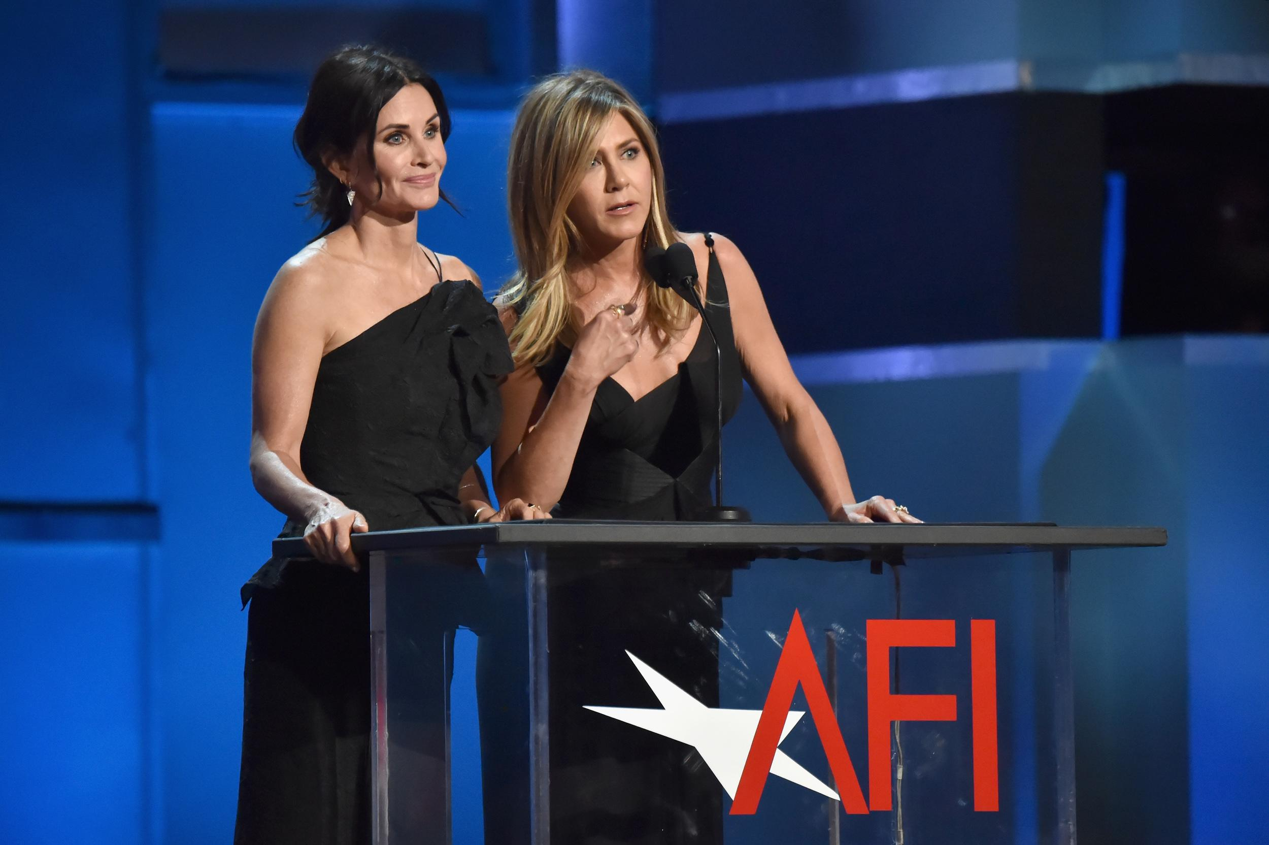 HOLLYWOOD, CA - JUNE 07:  Courteney Cox (L) and Jennifer Aniston speak onstage during the American Film Institute's 46th Life Achievement Award Gala Tribute to George Clooney at Dolby Theatre  on June 7, 2018 in Hollywood, California.  288523  (Photo by Kevin Mazur/Getty Images for Turner)