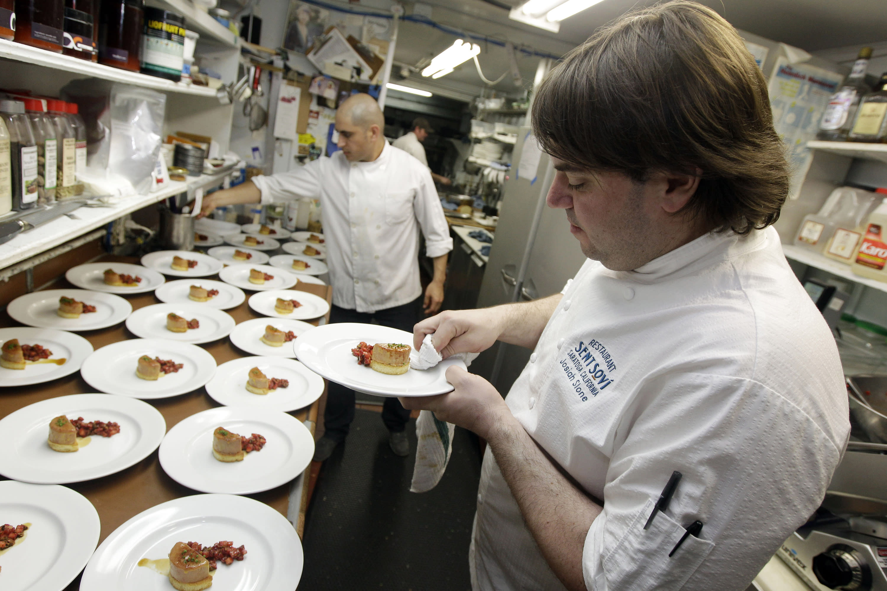 FILE - In this May 11, 2012, file photo, chef and owner Josiah Slone, right, prepares a foie gras dish at Sent Sovi restaurant in Saratoga, Calif. Foie gras is back on the menu in California after a judge ruled the rich dish can't be prevented from being brought in from out of state. California's ban on the delicacy, the fattened liver of a duck or goose, was challenged by out-of-state producers. An appeals court upheld the ban, but on Tuesday, July 14, 2020, a judge ruled for the plaintiffs, including farmers in Canada and New York. (AP Photo/Marcio Jose Sanchez, File)