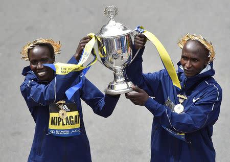 Los keniatas vencedores de la Maratón de Boston en la división femenina y masculina respectivamente, Edna Kiplagat y Geoffrey Kirui, celebran el trofeo durante la 121ª Maratón de Boston, Estados Unidos.
