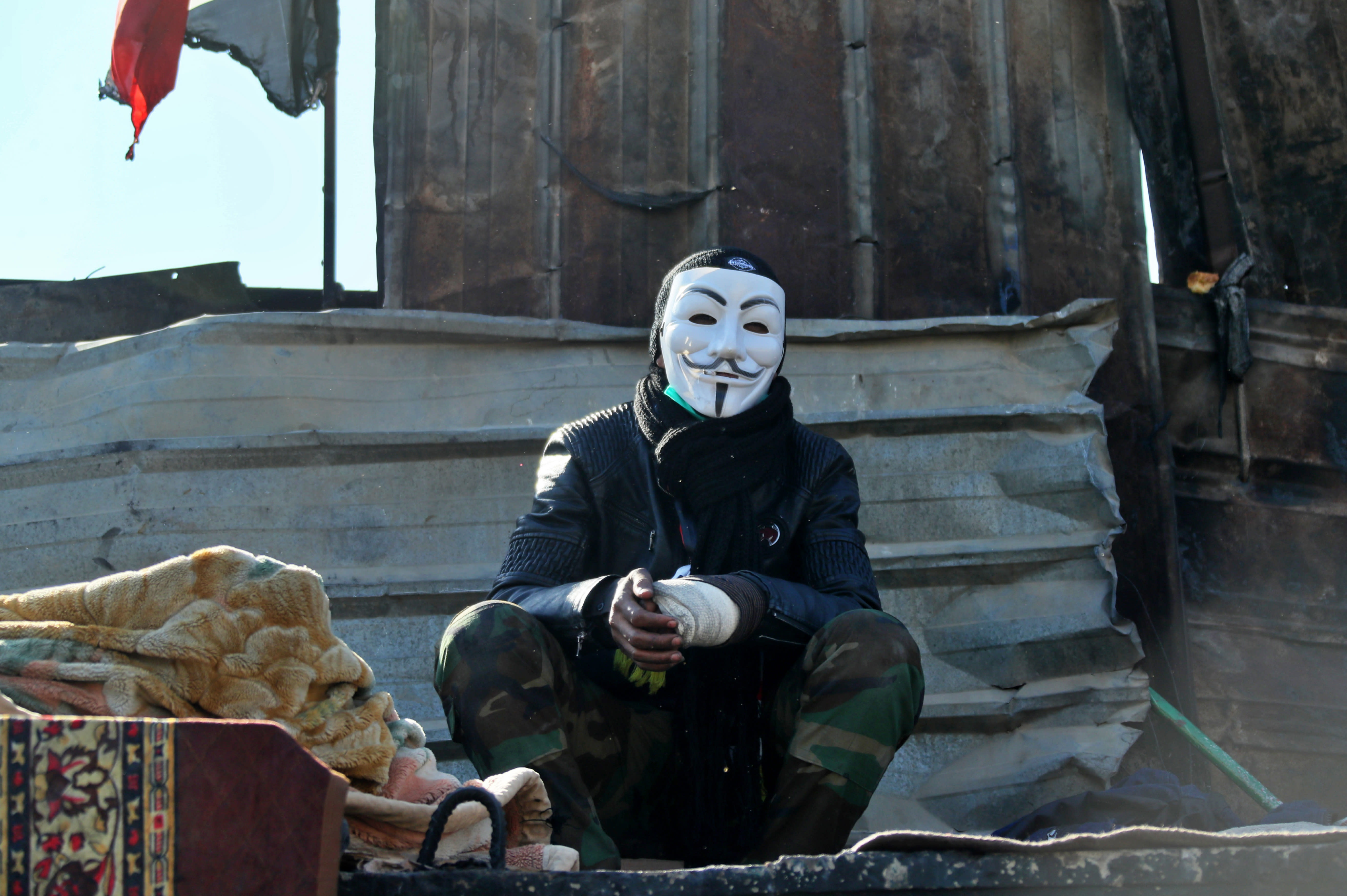 A protester wearing a Guy Fawkes mask takes part in a sit-in at the Ahrar Bridge in Baghdad, Iraq, Thursday, Nov. 21, 2019. Renewed clashes overnight in Baghdad between anti-government demonstrators and security forces killed and wounded protesters, security and hospital officials said Thursday. (AP Photo/Hadi Mizban)