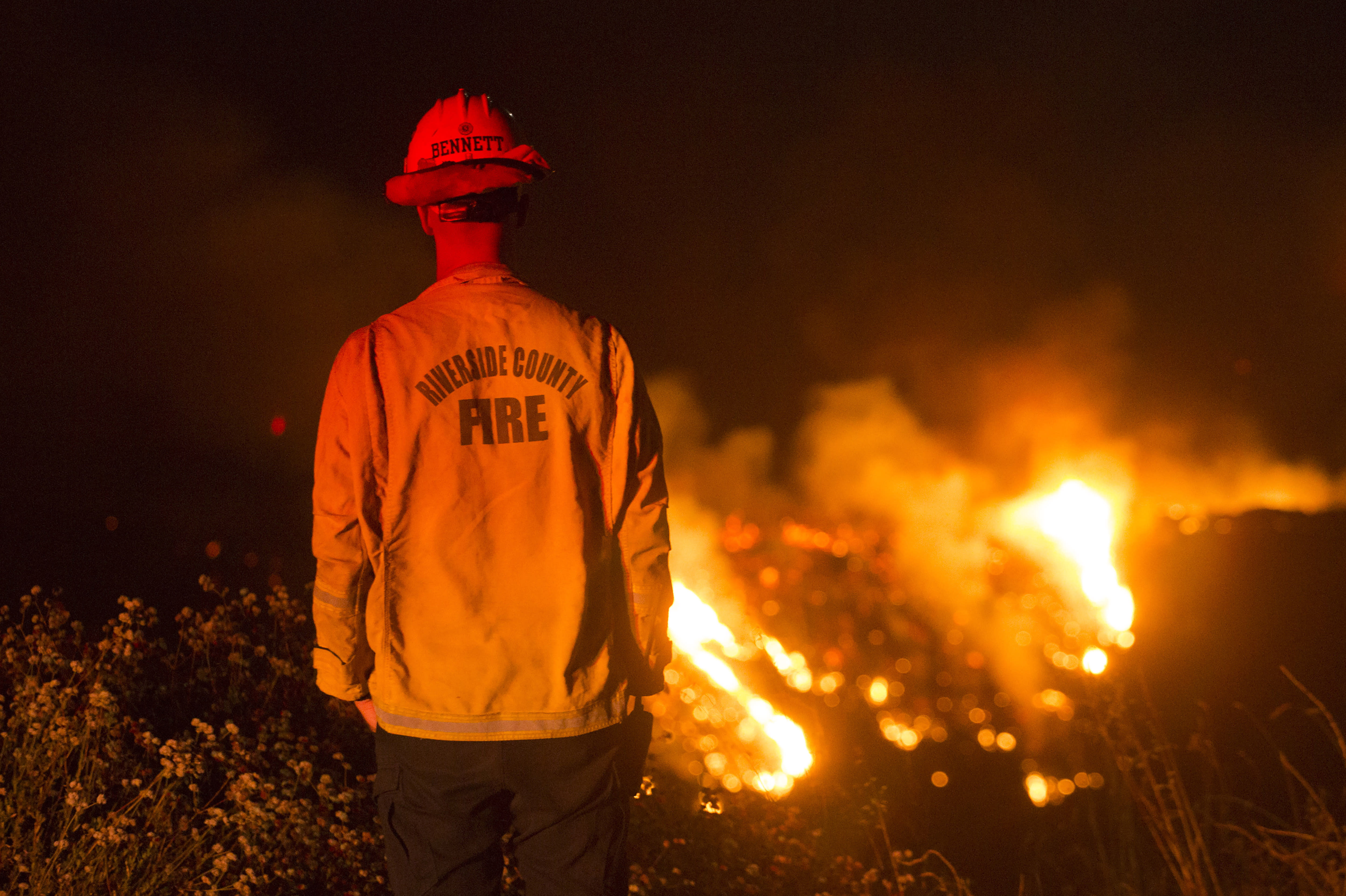 A firefighter watches a brush fire at the Apple Fire in Banning, Calif., Saturday, Aug. 1, 2020. (AP Photo/Ringo H.W. Chiu)