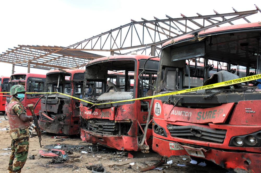 A photo taken on April 14, 2014 shows a soldier standing guard in front of burnt buses after an attack in Abuja, Nigeria (AFP Photo/)