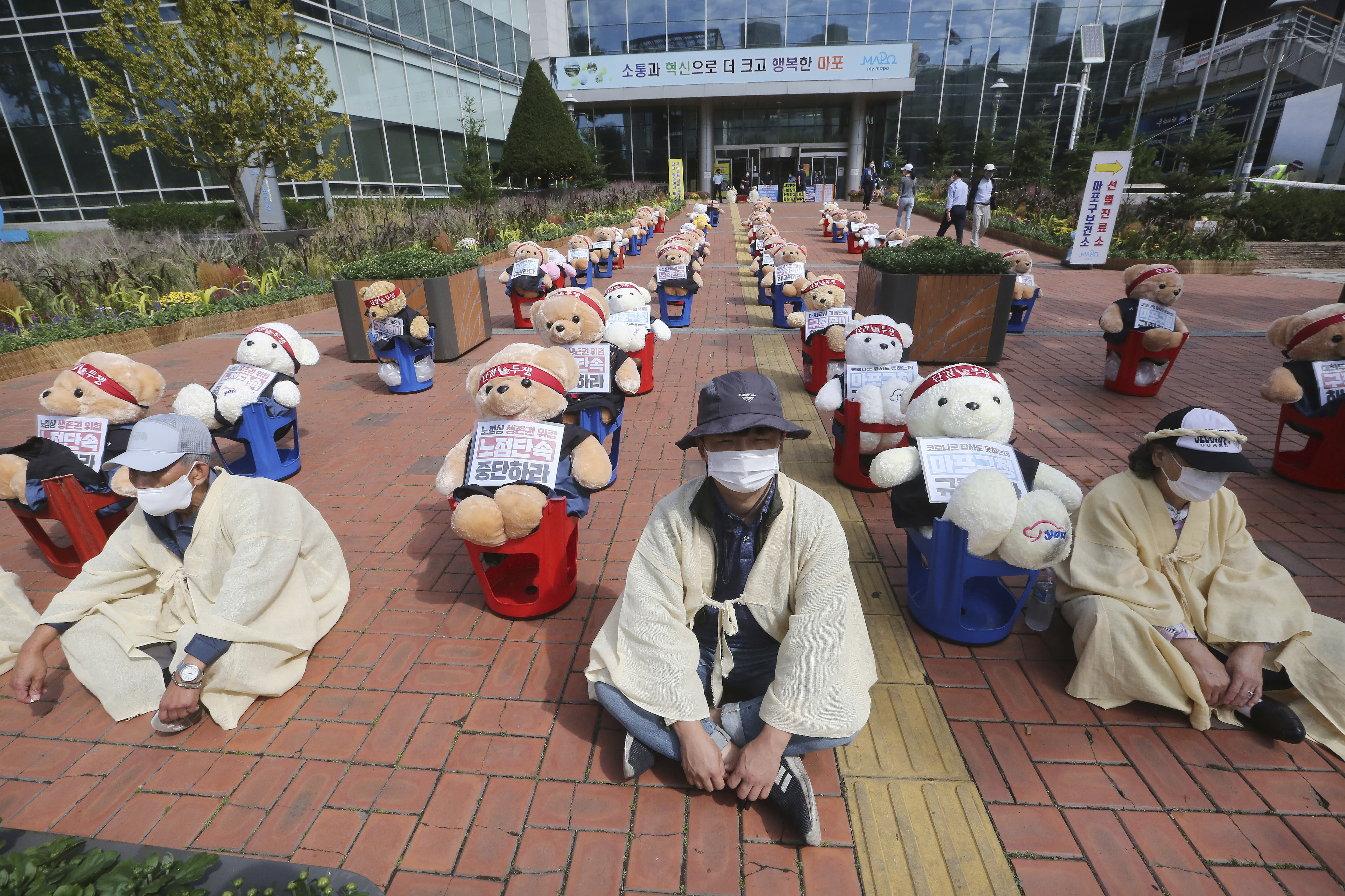 """Street vendors sit to protest against a crackdown on illegal street vendors, in front of the Mapo ward office in Seoul, South Korea, Thursday, Sept. 24, 2020. They replaced protestors with teddy bears to avoid the violation of an ongoing ban on rallies with more than 10 people amid the coronavirus pandemic. The signs read: """"Stop crackdown."""" (AP Photo/Ahn Young-joon)"""