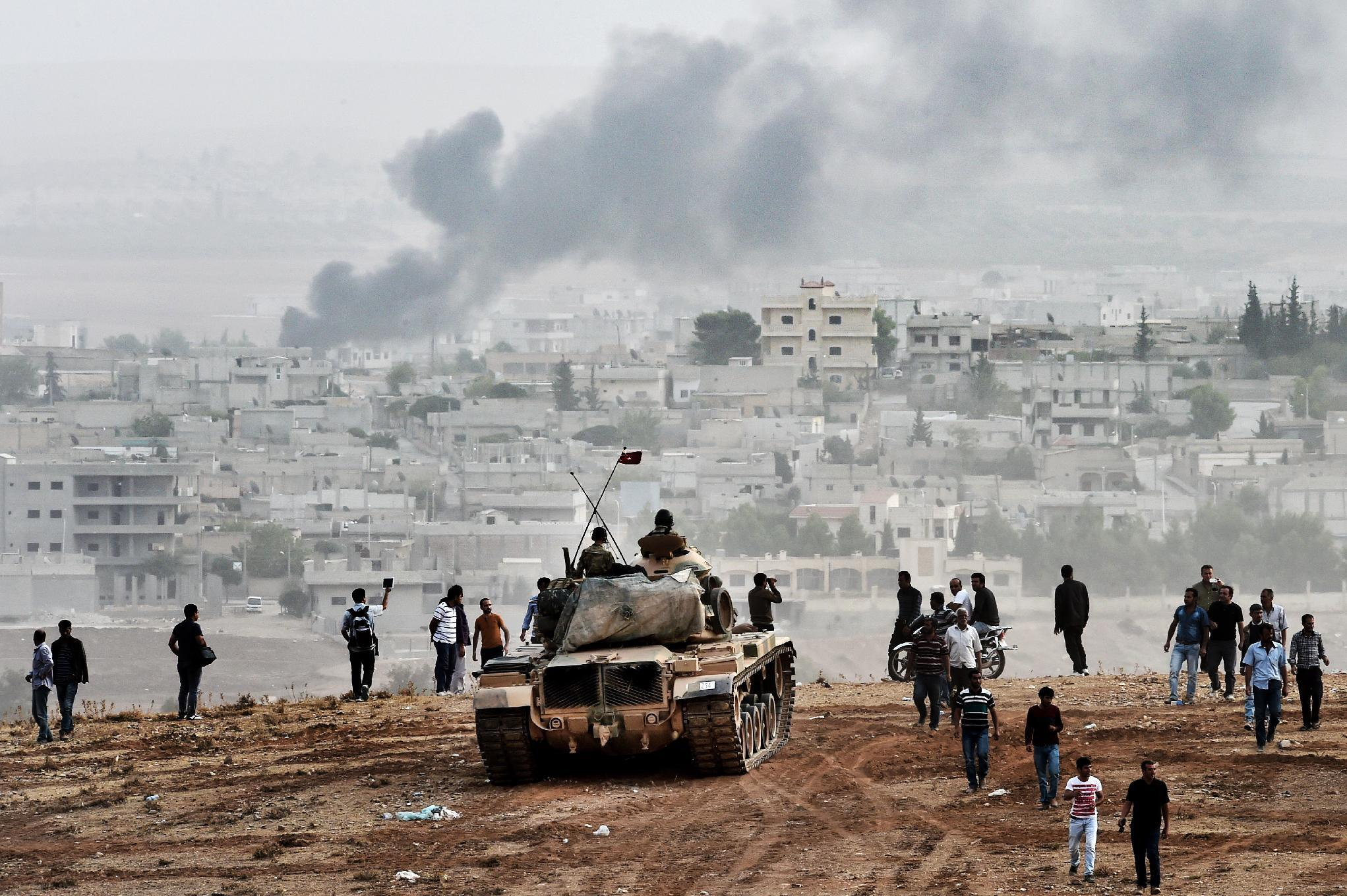Turkish soldiers on a tank and Kurdish people look at the Syrian town of Kobane, from a hill near the Turkish-Syrian border, on October 11, 2014 (AFP Photo/Aris Messinis)