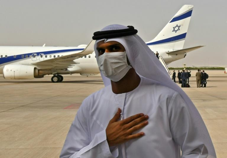 An Emirati official stands near the El Al plane that flew the first-ever direct commercial service from Israel to the UAE