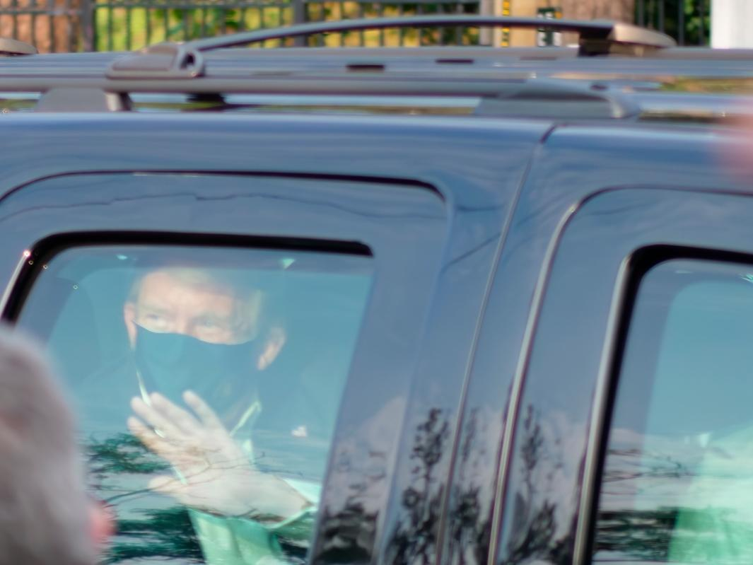 President Donald Trump drives past supporters gathered outside Walter Reed National Military Medical Center in Bethesda, Md., Sunday, Oct. 4, 2020. Trump was admitted to the hospital after contracting COVID-19