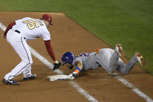 New York Mets' Robinson Chirinos, right, slides safely into first against Washington Nationals starting pitcher Patrick Corbin (46) during the sixth inning of a baseball game, Thursday, Sept. 24, 2020, in Washington. The Mets won 3-2. (AP Photo/Nick Wass)