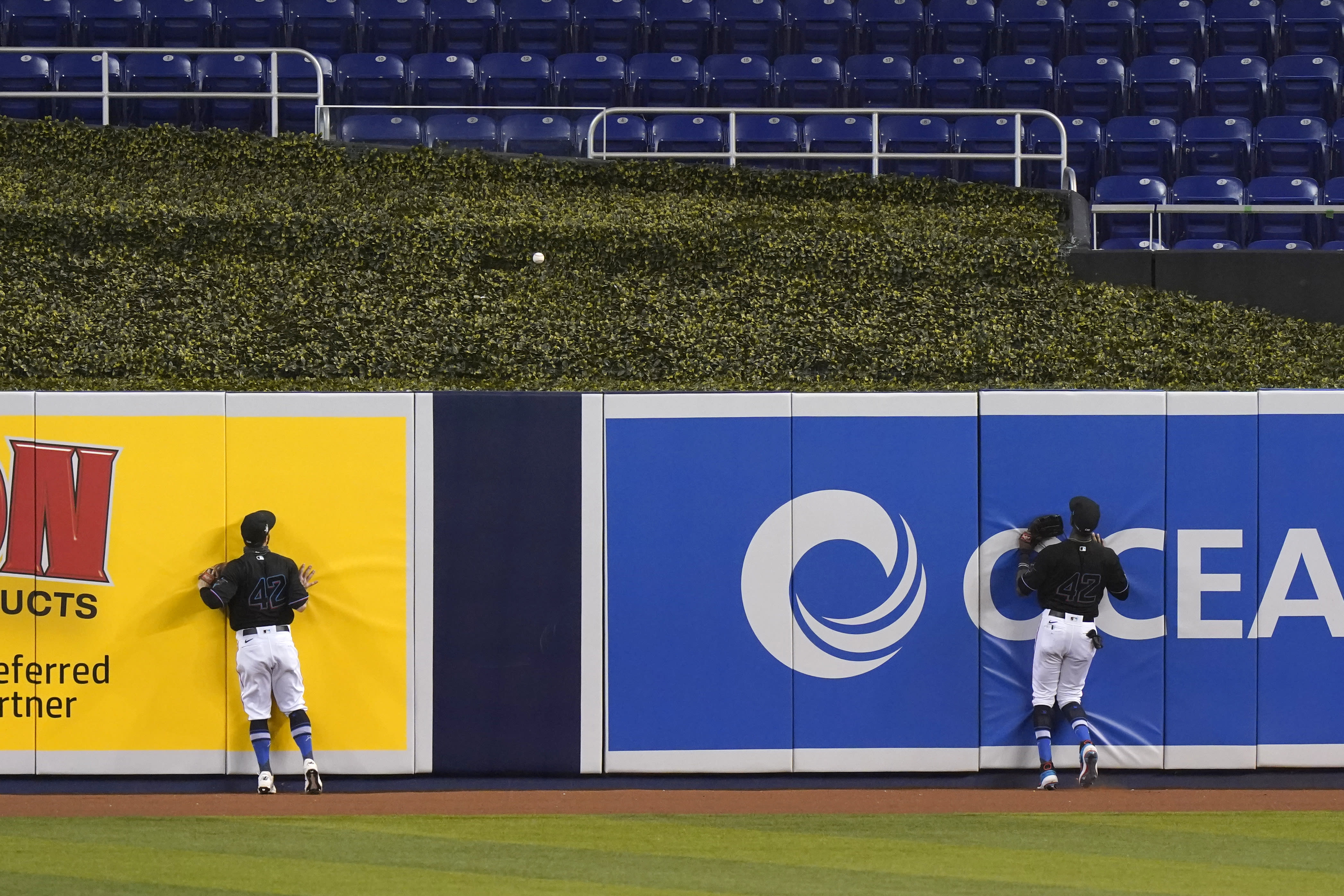 Outfielders Jon Berti, left, and Lewis Brinson watch as a ball hit by Tampa Bay Rays' Yoshitomo Tsutsugo goes over the wall for a two-run home run during the first inning of a baseball game, Sunday, Aug. 30, 2020, in Miami. (AP Photo/Wilfredo Lee)