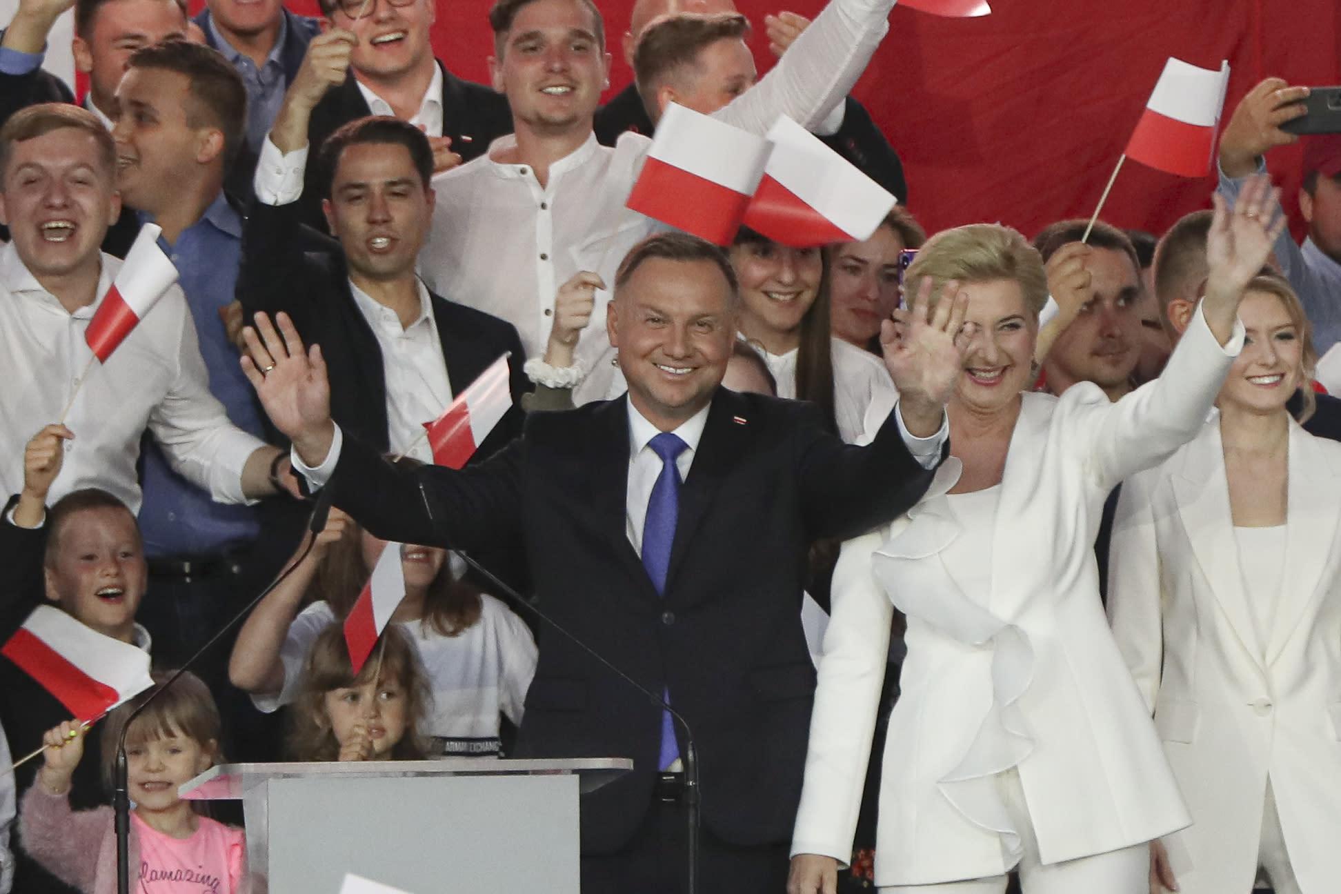 El presidente Andrzej Duda, acompañado por su esposa Agata Kornhauser-Duda, saluda a sus simpatizantes el domingo 12 de julio de 2020, en Pultusk, Polonia. (AP Foto/Czarek Sokolowski)