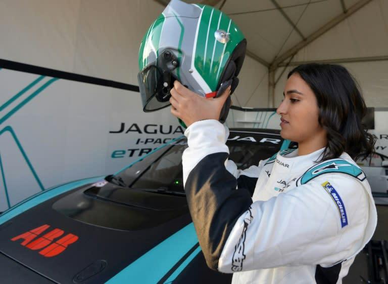 Saudi Arabia's first woman racing driver Reema al-Juffali adjusts her helmet in front of her car (AFP Photo/FAYEZ NURELDINE)