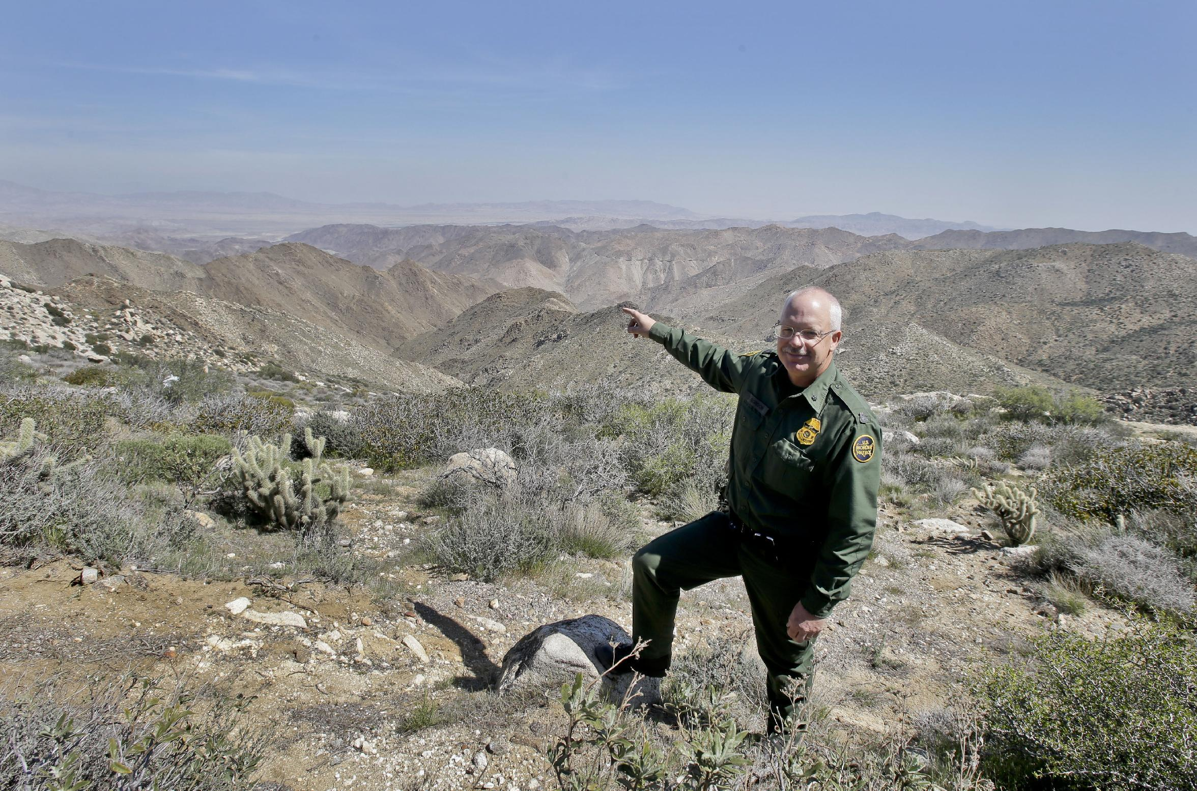 """In this Monday, March 25, 2013 photo, Border Patrol agent Richard Gordon, a 23-year veteran of the agency, points to a route used by illegal immigrants that runs through rugged mountainous terrain in the Boulevard area east of San Diego, in Boulevard, Calif. For the past 16 years, Gordon has been one of the top """"sign-cutters"""" or trackers in the Border Patrol. (AP Photo/Lenny Ignelzi)"""