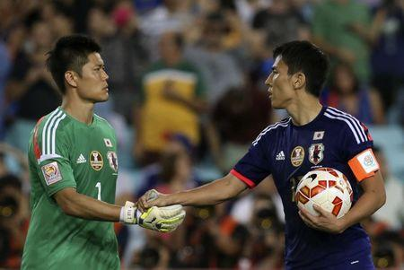 Japan's Makoto Hasebe shakes hands with goalkeeper Eiji Kawashima during the penalty shoot out in their Asian Cup quarter-final soccer match against UAE at the Stadium Australia in Sydney