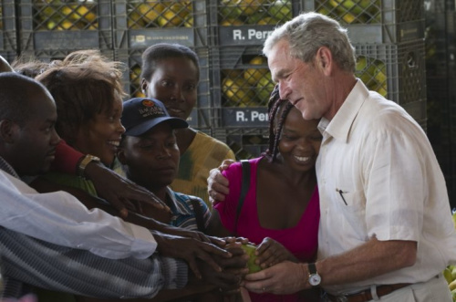 Former President George W. Bush, right, shares a moment with workers of a mango warehouse in Port-au-Prince, Haiti, Tuesday Aug. 10, 2010. Bush arrived in Haiti on Tuesday, to visit organizations, supported by the Clinton-Bush Haiti Fund, and to reassure investors that the money spent would help the nation