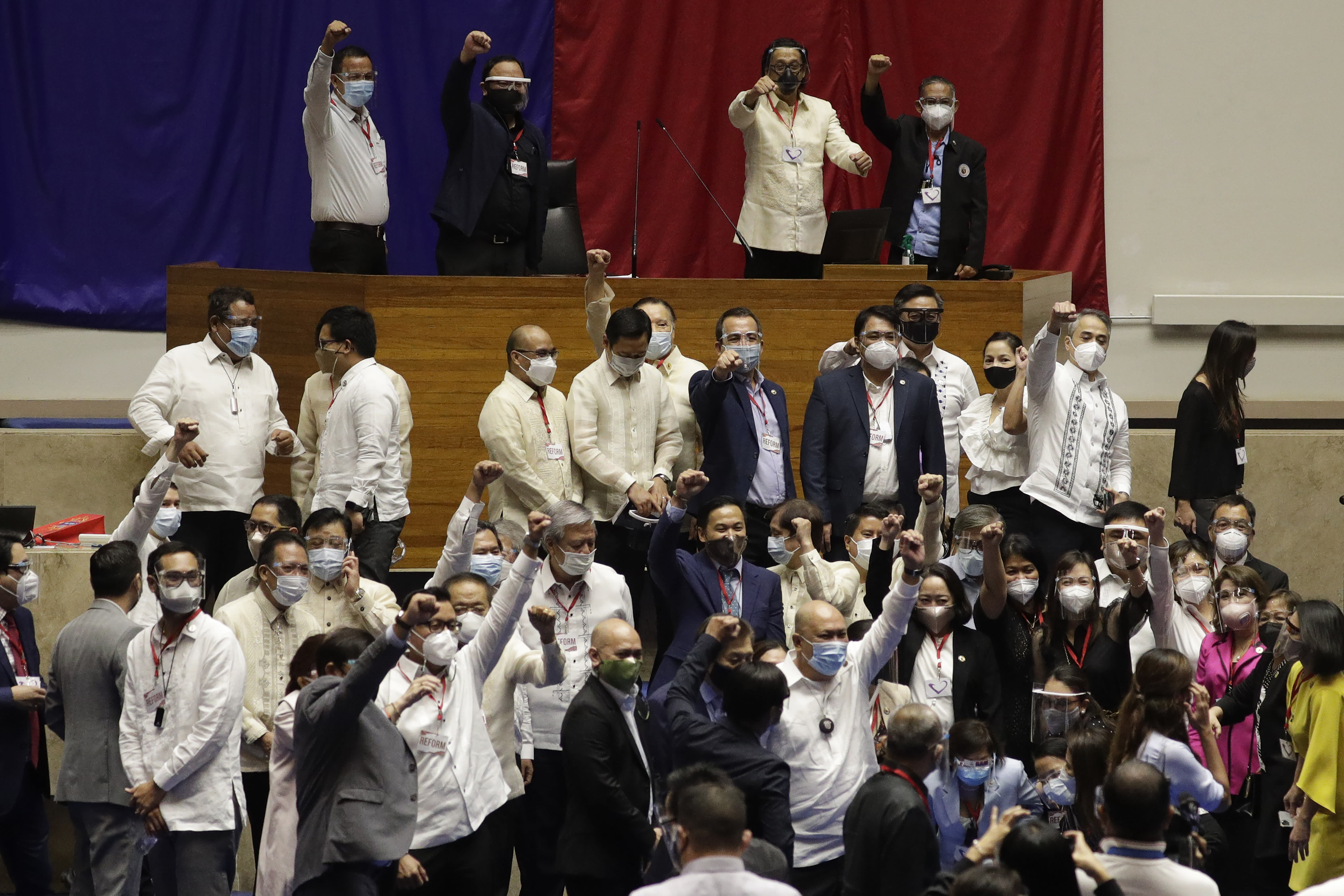Supporters of new house speaker Lord Allan Velasco gestures after posing for pictures at the House of Representatives in Quezon city, Philippines on Tuesday, Oct. 13, 2020. A large faction of Philippine legislators in the House of Representatives elected a new leader Monday in a tense political standoff between two allies of the president. (AP Photo/Aaron Favila)