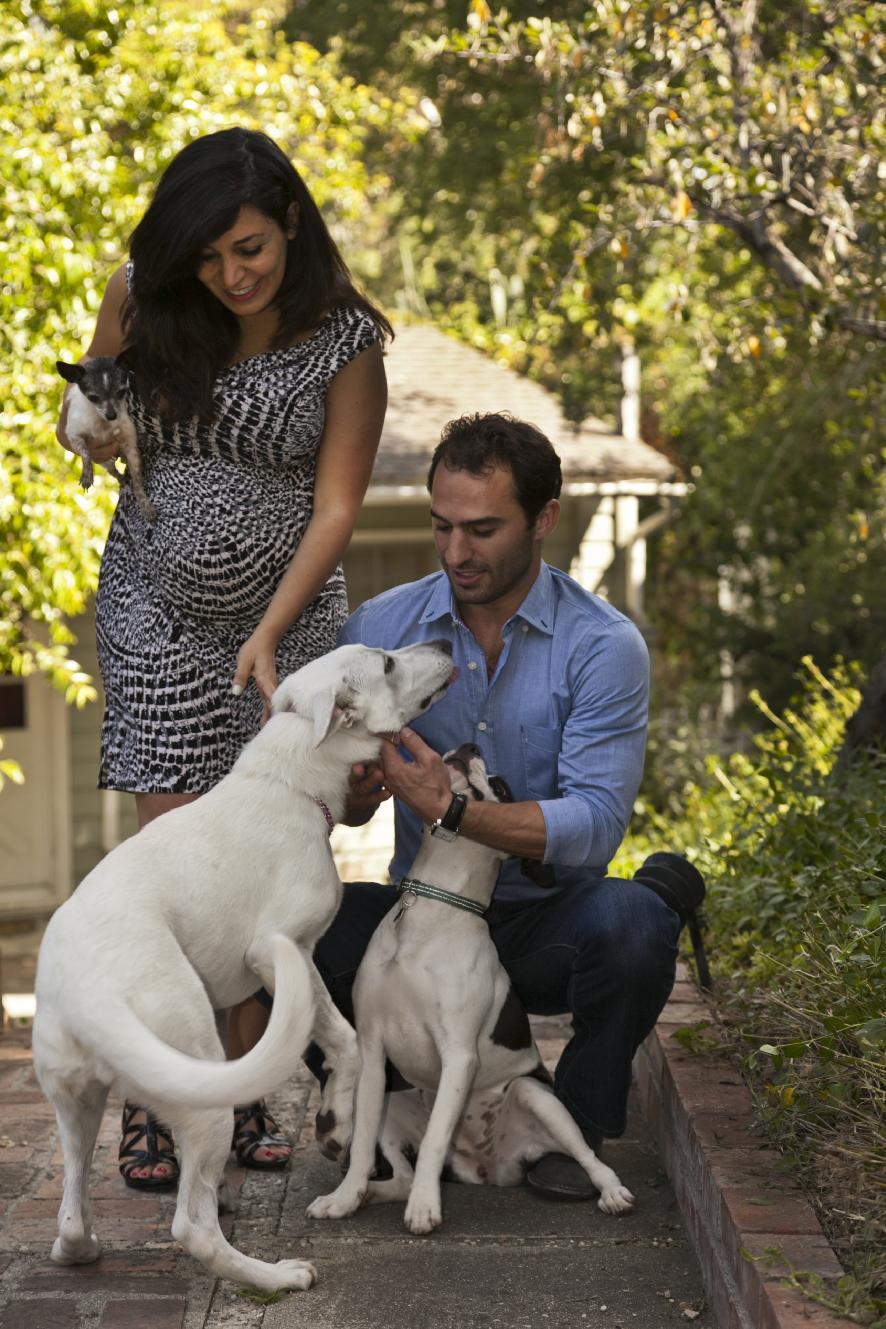 In this photo taken Friday, May 11, 2012, husband and wife entrepreneurs Aaron and Karine Hirschhorn pose with hosted dogs at a home in Los Angeles. Instead of putting pets in kennels, Dog Vacay brings together dog lovers with casual and professional dog sitters to provide an affordable experience for pets. (AP Photo/Damian Dovarganes)