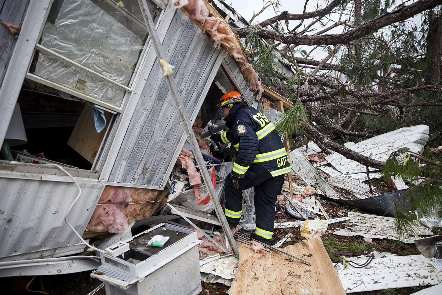 <p>A rescue worker enters a hole in the back of a mobile home Monday, Jan. 23, 2017, in Big Pine Estates that was damaged by a tornado, in Albany, Ga. (AP Photo/Branden Camp) </p>