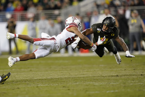 FILE - In this Dec. 6, 2018, file photo, Oregon safety Jevon Holland (8) breaks up a pass for Utah wide receiver Jaylen Dixon (25) during the first half of the Pac-12 Conference championship NCAA college football game in Santa Clara, Calif. A group of Pac-12 football players on Sunday, Aug. 2, 2020, threatened to opt out of the coming season unless its concerns about competing during the COVID-19 pandemic and other racial and economic issues in college sports are addressed. (AP Photo/Tony Avelar, File)