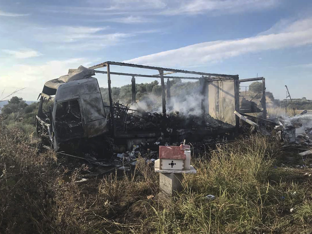 A burnt out truck on a field behind a small chapel, next to a motorway, following a collision near Greece's northern town of Kavala, Saturday, Oct. 13, 2018. A car carrying migrants collided with a truck in northern Greece on Saturday, killing 11 people, police said. (Proininews.gr via AP)