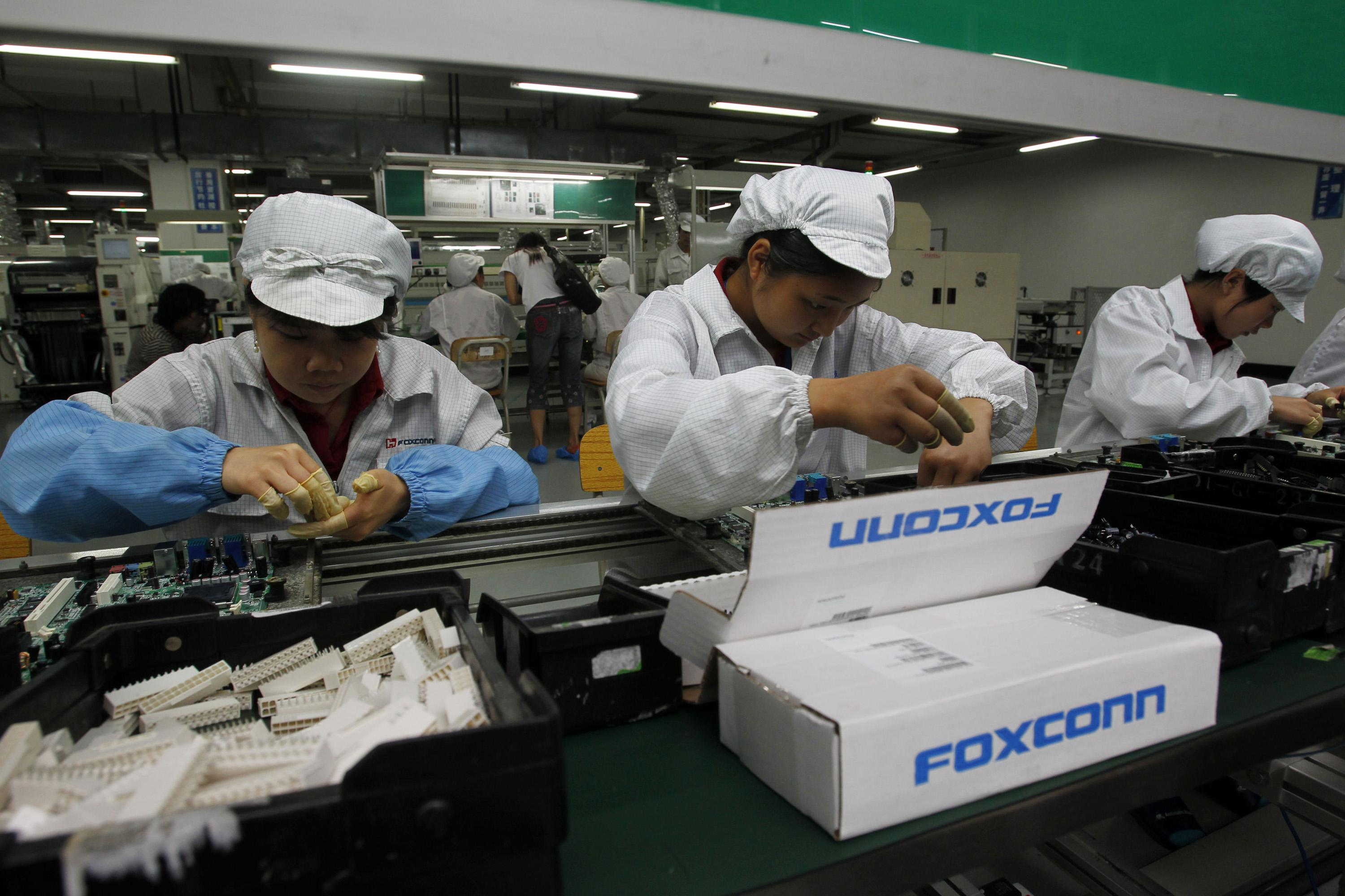 FILE - In this May 26, 2010 file photo, staff members work on the production line at the Foxconn complex in the southern Chinese city of Shenzhen, southern China. A pledge reported Thursday, March 29, 2012 by the manufacturer of Apple's iPhones and iPads to limit work hours at its factories in China could force other global corporations to hike pay for Chinese workers who produce the world's consumer electronics, toys and other goods. Foxconn Technology's promise comes as Beijing is pushing foreign companies to share more of their revenues with Chinese employees. (AP Photo/Kin Cheung, File)