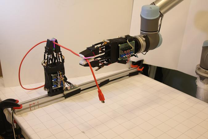 A picture of MIT's new robot handling a USB cable.