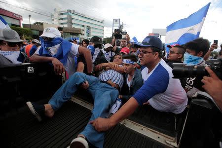 Demonstrators help an injured man during a protest against Nicaraguan President Daniel Ortega's government in Managua