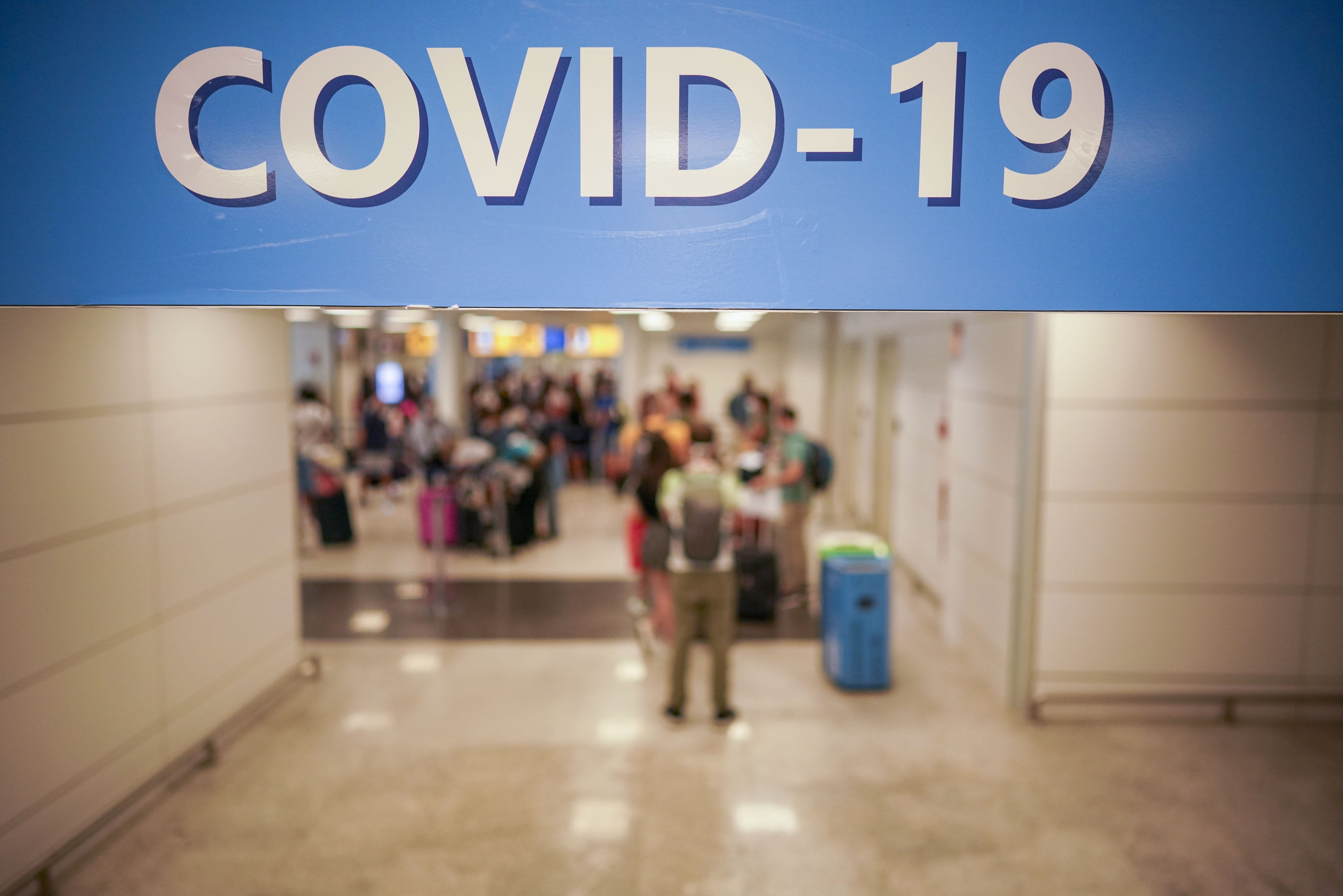 Vacationers arriving in Rome from four Mediterranean countries line up with their suitcases at Rome's Leonardo da Vinci airport to be immediately tested for COVID-19, Sunday, Aug.16, 2020. Italy's health minister issued an ordinance requiring the tests for all travelers arriving in Italy from Croatia, Greece, Malta or Spain. (AP Photo/Andrew Medichini)