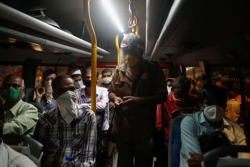 A conductor counts money on a bus amidst the spread of the coronavirus disease (COVID-19) in Mumbai