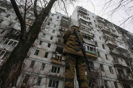 Pro-Russian separatist stands guard in front of a building damaged during fighting between pro-Russian rebels and Ukrainian government forces near Donetsk Sergey Prokofiev International Airport, eastern Ukraine