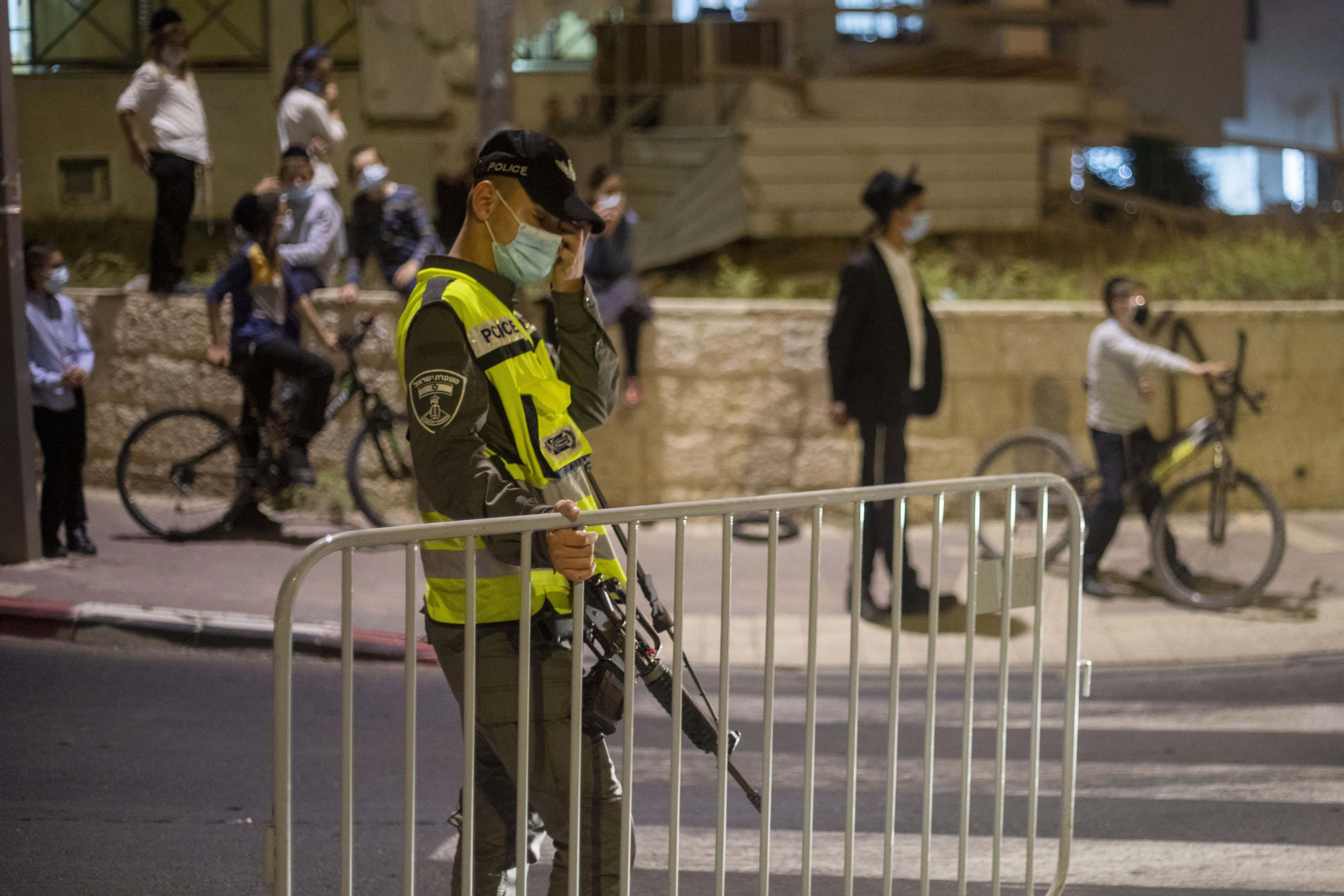 An Israeli border police man setups a barrier as ultra-Orthodox Jews wearing face masks amid the coronavirus pandemic wait to cross the street during an overnight curfew in Beit Shemes, Israel, Tuesday, Sept. 8, 2020. Israeli Prime Minister Benjamin Netanyahu announced overnight curfews on some 40 cities and towns hit hard by the coronavirus. (AP Photo/Ariel Schalit)