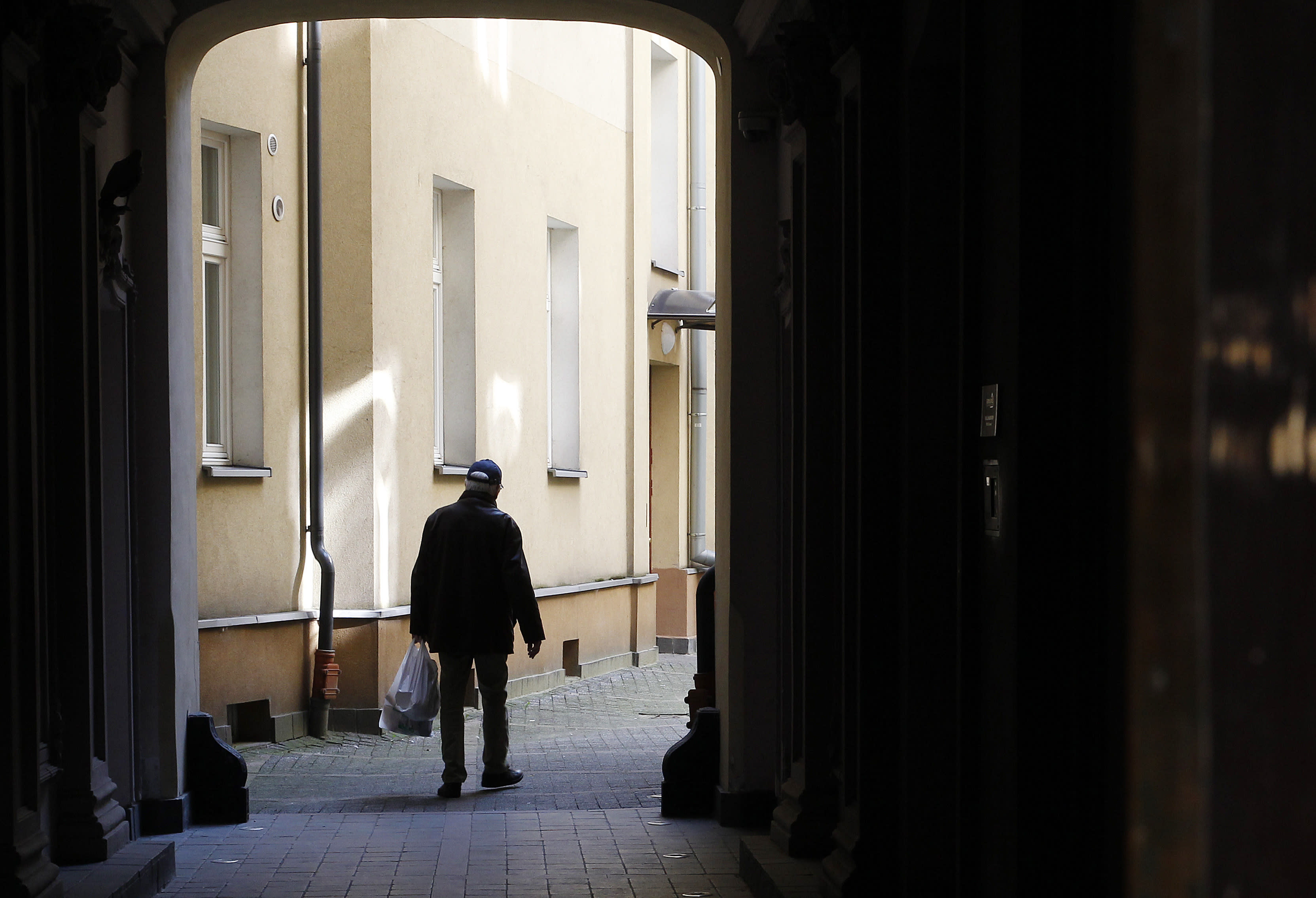 An elderly man returns home with his shopping, which is one of the very few outdoor activities allowed under a national quarantine against the spread of the coronavirus, in Warsaw, Poland, on Thursday, March 26, 2020. The new coronavirus causes mild or moderate symptoms for most people, but for some, especially older adults and people with existing health problems, it can cause more severe illness or death.(AP Photo/Czarek Sokolowski)