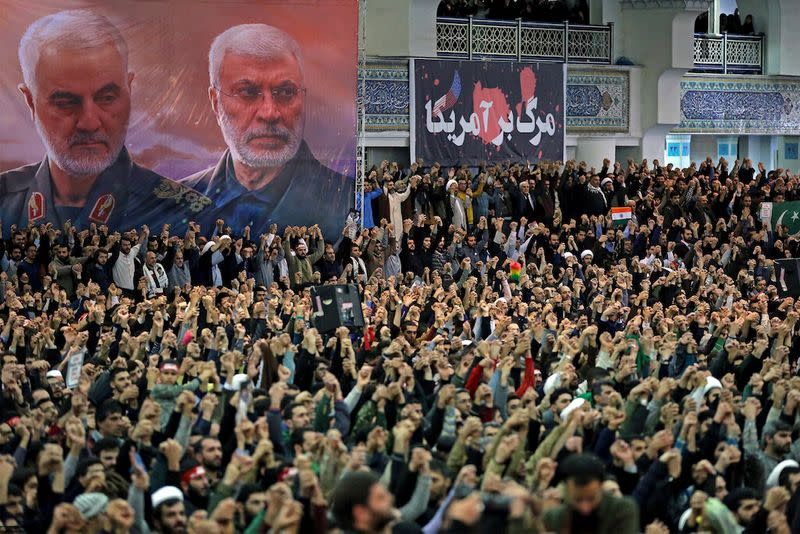 A poster shows late Iranian military commander Qassem Soleimani and late Iraqi militia commander Abu Mahdi al-Muhandis, as Iranian worshippers chant slogans during the Friday prayers sermon led by Iran's Supreme Leader Ayatollah Ali Khamenei, in Tehran